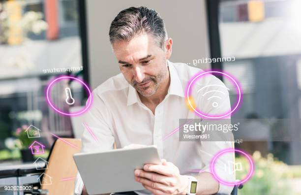 man sitting in office, using digital tablet to remote-control his smart home - remote controlled stock photos and pictures