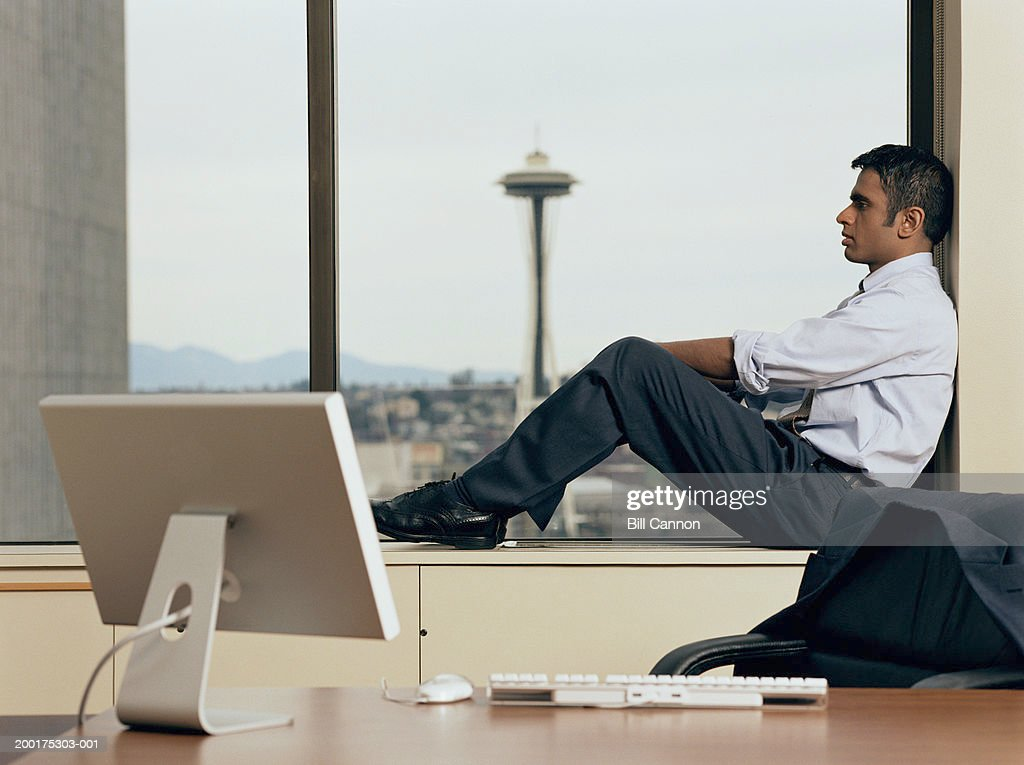 Man Sitting In Office Window Side View Stock Photo