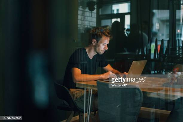 man sitting in office, working late in his start-up company - working overtime stock pictures, royalty-free photos & images