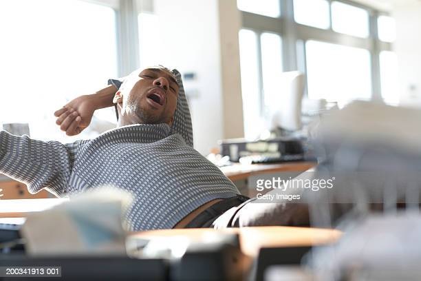 Man sitting in office, yawning