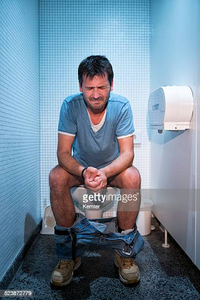 man sitting in public restroom - toilet stockfoto's en -beelden