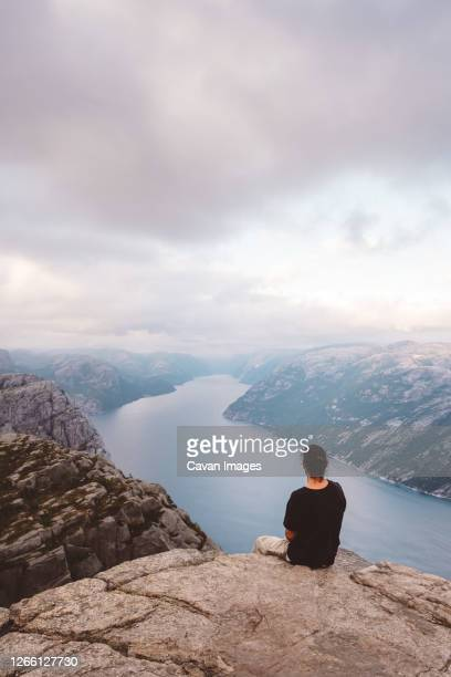 man sitting in rock at edge of cliff at preikestolen, norway - one man only stock pictures, royalty-free photos & images