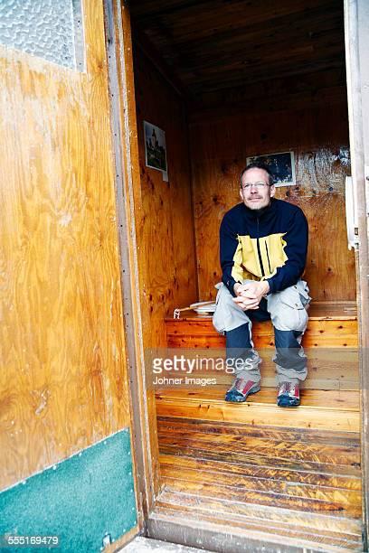 man sitting in sauna - gemak stockfoto's en -beelden