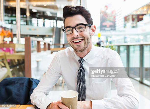 Man sitting in shopping area with coffee.
