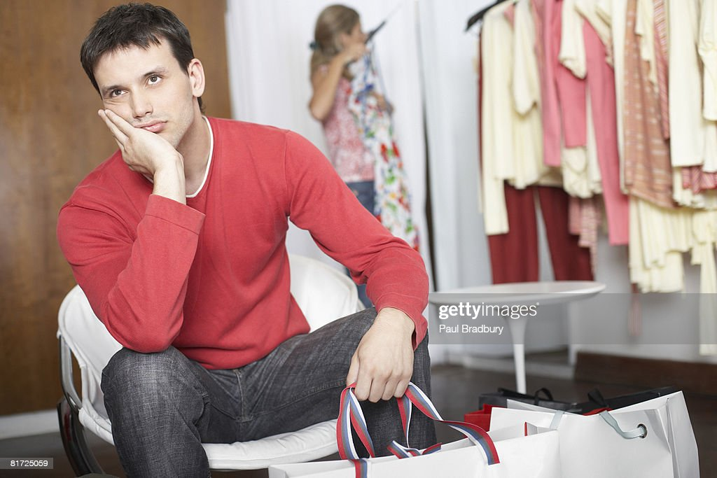 Man sitting in store waiting and looking bored : Stock Photo