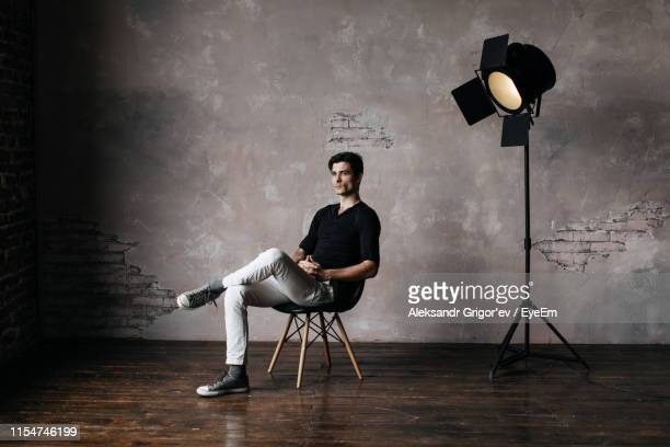 man sitting in studio - fotosession stock-fotos und bilder