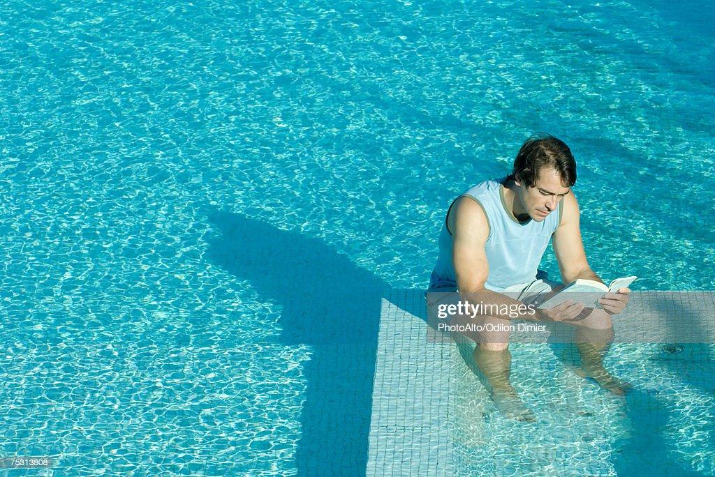 Man sitting in swimming pool, reading : Stock Photo