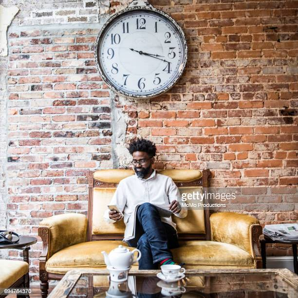 Man sitting in teashop under large clock