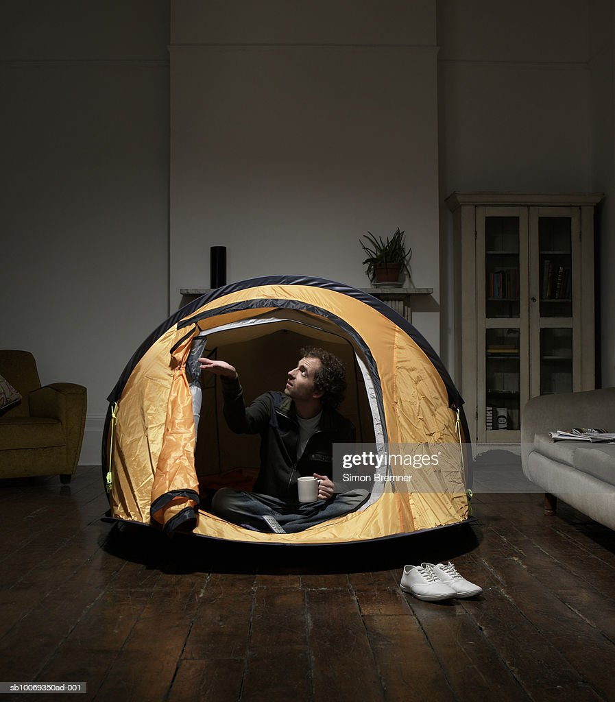 Man sitting in tent in living room  Stock Photo & Man Sitting In Tent In Living Room Stock Photo | Getty Images