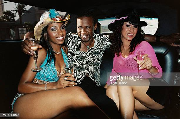 man sitting in the back seat of a limousine with his arms around two women - clubkleding stockfoto's en -beelden