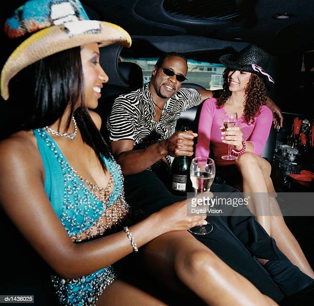 man sitting in the back seat of a limousine with two women drinking champagne - man met een groep vrouwen stockfoto's en -beelden