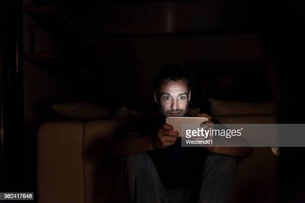 man sitting in the dark at home starring at smartphone - staring stock photos and pictures