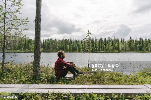 man sitting in the forest near the river - finland stock pictures, royalty-free photos & images
