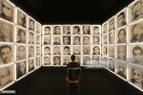 A man sitting in the middle of a room in an installation depicting madmen without a mouth in the museum of madness