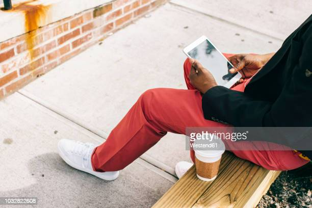 Man sitting in the street, using digital tablet, drinking coffee