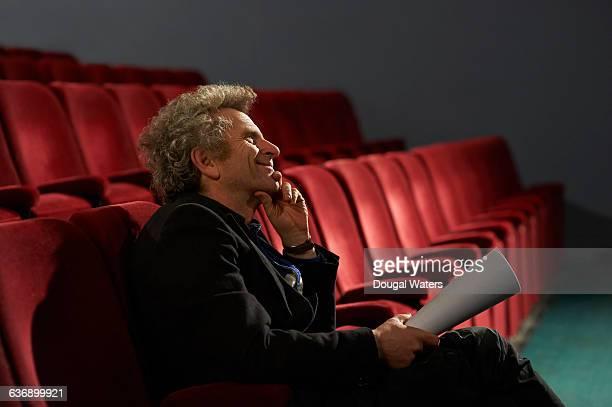 man sitting in theatre chair with script. - acteur photos et images de collection