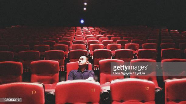 man sitting in theatre - seat stock pictures, royalty-free photos & images
