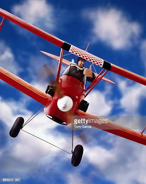 Man sitting in toy biplane, giving thumbs up signal (Composite)