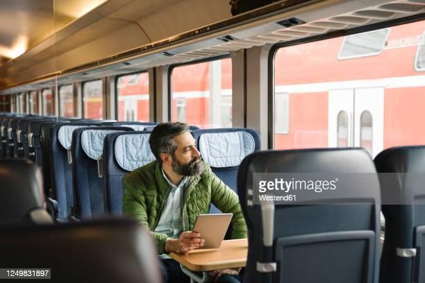 man sitting in train holding tablet - bahnreisender stock-fotos und bilder