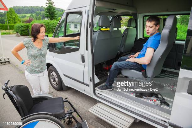 man sitting in van while woman standing by wheelchair on road - seulement des adultes photos et images de collection
