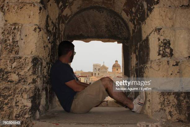 Man Sitting In Window At Torre (no Suggestions) Against Cagliari Cathedral