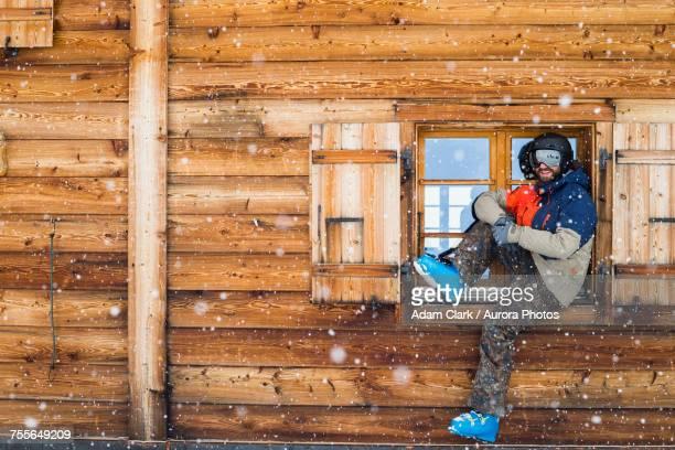 man sitting in window of log cabin in full ski gear, verbier, switzerland - ウィンタースポーツ ストックフォトと画像