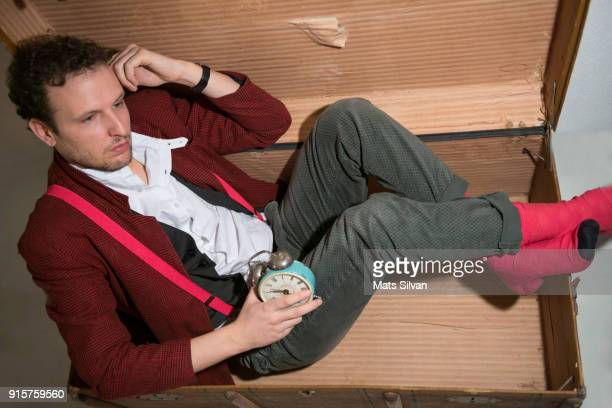 Man Sitting Inside a Box and Daydreaming