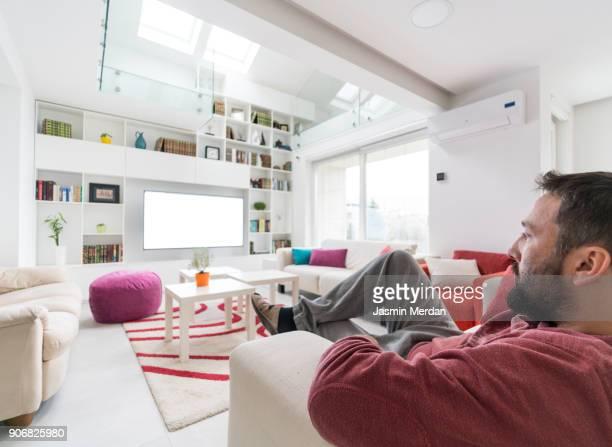 Man sitting inside modern white home interior