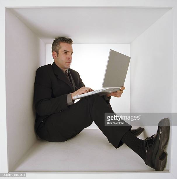 Man sitting inside white box, working on laptop computer