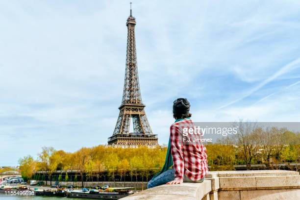 man sitting looking towards the eiffel tower - france stock pictures, royalty-free photos & images