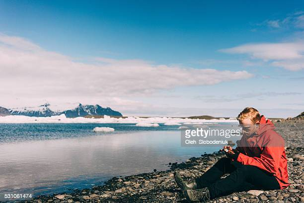 Man sitting near the lake with glaciers