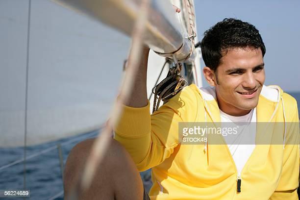 Man sitting next to a sail