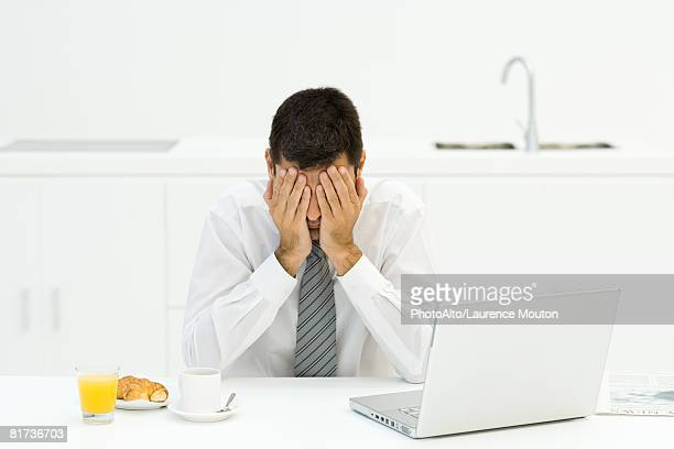 man sitting next to breakfast and laptop, covering face with hands - obscured face stock pictures, royalty-free photos & images