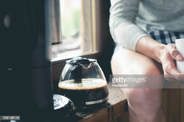 Man sitting next to coffee pot on window sill