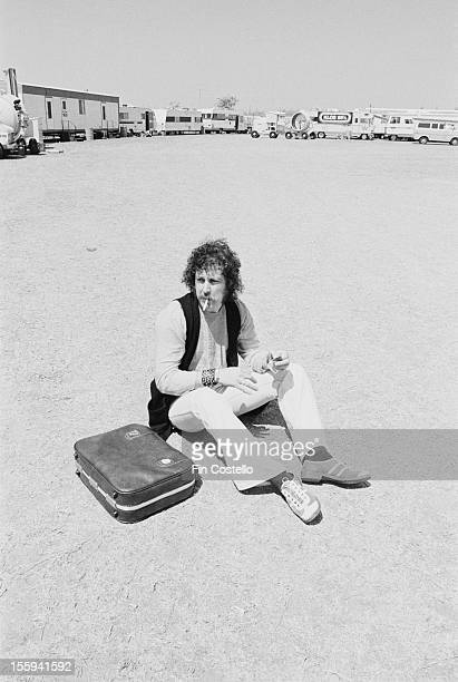 Man sitting next to his overnight bag and smoking a cigarette at the California Jam rock festival, Ontario Motor Speedway, Ontario, California, 6th...