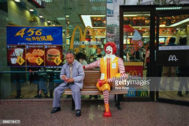 man sitting next to ronald mcdonald statue - mcdonald's stock pictures, royalty-free photos & images