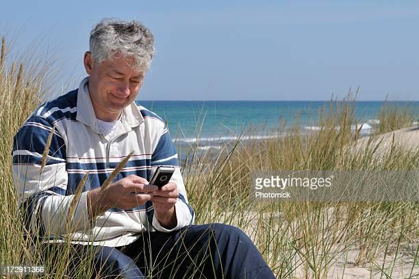 Mann sitzt auf einem Strand, die mobile e-mail-Adresse