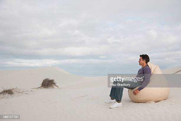 A man sitting on a beanbag chair outdoors