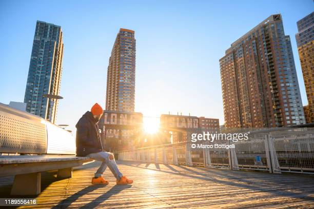 man sitting on a bench admiring the sunrise from a pier in long island, new york state - long island stock pictures, royalty-free photos & images