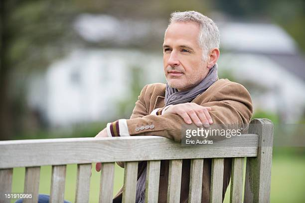 Man sitting on a bench and thinking in a park