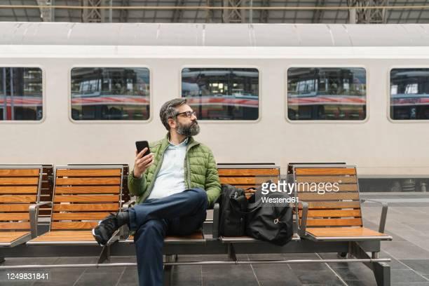 man sitting on a bench at the train station - bahnreisender stock-fotos und bilder