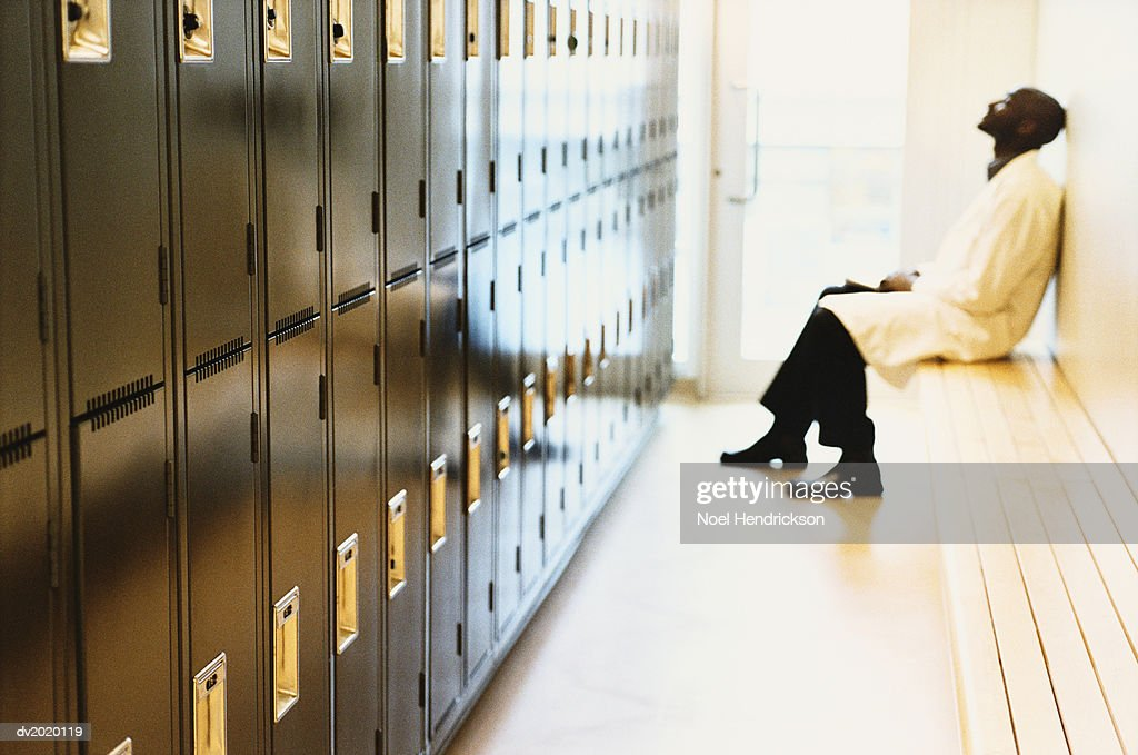 Man Sitting on a Bench in a Locker Room : Stock Photo