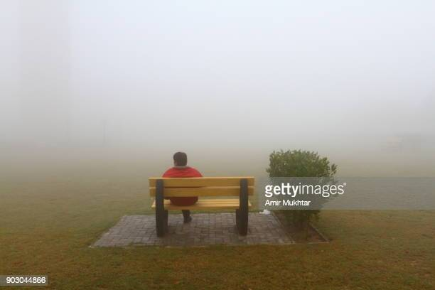Man Sitting On A Bench In The Fog
