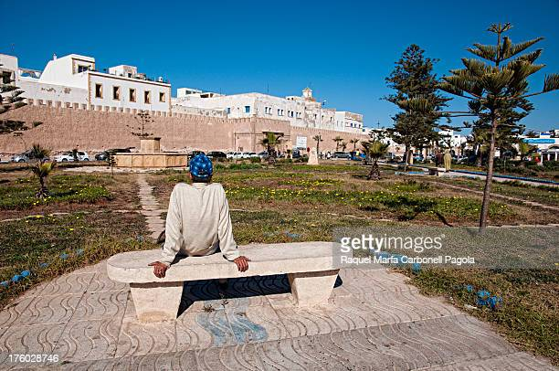 Man sitting on a bench of a park in front of Essaouira medina wall, Essaouira, World Heritage site, Morocco. 2013