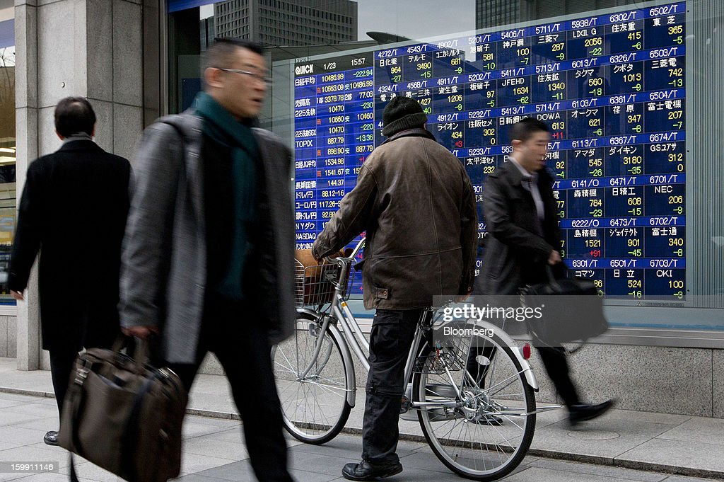 A man sitting on a bicycle looks at a stock board outside a securities firm as pedestrians walk past in Tokyo, Japan, on Wednesday, Jan. 23, 2013. Japan shares declined, with the Nikkei 225 Stock Average posting its first three-day decline since elections were called, as the yen climbed after the Bank of Japan said it will wait a year to add open-ended stimulus. Photographer: Tomohiro Ohsumi/Bloomberg via Getty Images