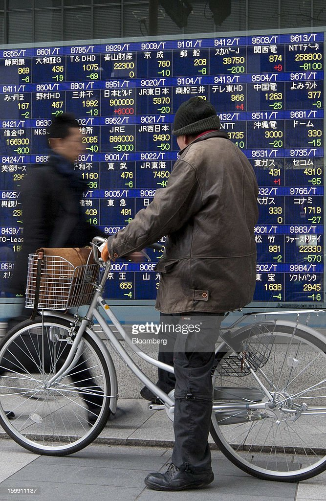 A man sitting on a bicycle looks at an electronic stock board outside a securities firm in Tokyo, Japan, on Wednesday, Jan. 23, 2013. Japan shares declined, with the Nikkei 225 Stock Average posting its first three-day decline since elections were called, as the yen climbed after the Bank of Japan said it will wait a year to add open-ended stimulus. Photographer: Tomohiro Ohsumi/Bloomberg via Getty Images