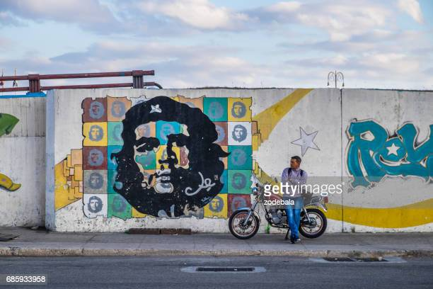 man sitting on a bike and mural of ernesto che guevara in cuba - cuban revolution stock photos and pictures