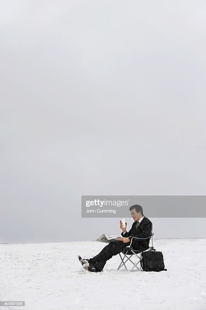 Man Sitting on a Chair Outdoors in Snow and Reading a Newspaper : Stock Photo