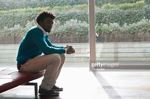 Man sitting on a couch and thinking