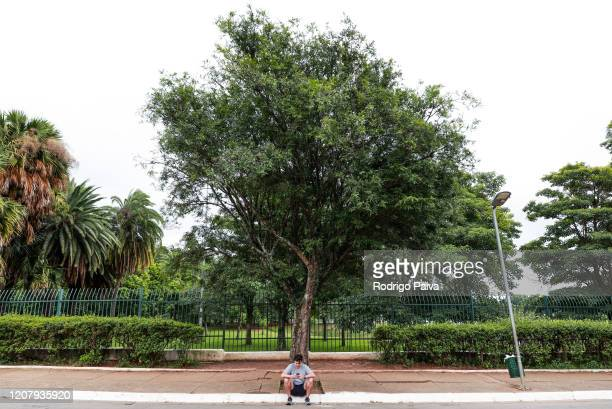 A man sitting on a curb outside the gates of Ibirapuera Park checks his phone during a lockdown aimed at stopping the spread of the coronavirus...